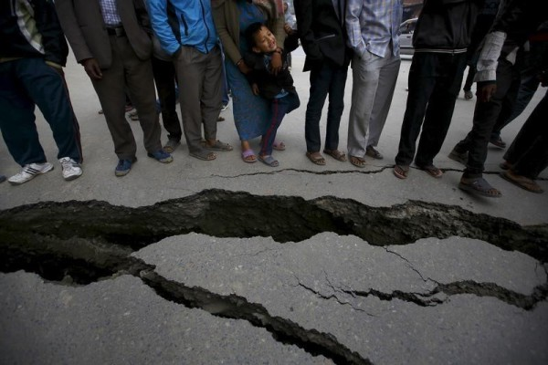 People gather near the cracks on the road caused by an earthquake in Bhaktapur, Nepal April 26, 2015. Rescuers dug with their bare hands and bodies piled up in Nepal on Sunday after an earthquake devastated the heavily crowded Kathmandu valley, killing at least 1,900, and triggered a deadly avalanche on Mount Everest.  REUTERS/Navesh Chitrakar      TPX IMAGES OF THE DAY      - RTX1AANP